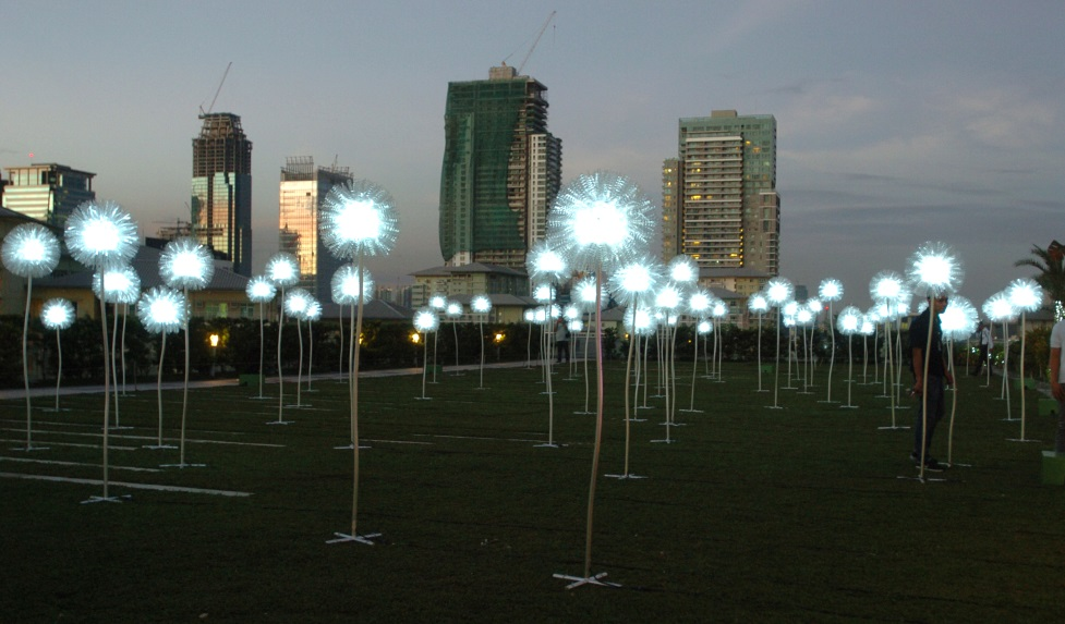 Displayed on the SM Aura Skypark lawn, Olivia d'Aboville's Giant Dandelions features flowers of different heights with dandelion heads made from recycled water bottles. The art installation was in line with SM Supermalls' efforts in promoting environmental awareness and eco-friendly sustainable development.